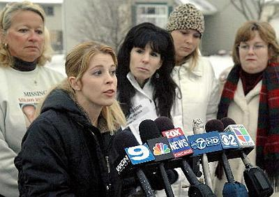 [Nicole Goyette addresses the media as Susan Olsen (from left) Stephanie NcNeil, Kerry Simmons and Melanie Greenberg stand-by Monday afternoon during a press conference for their missing loved ones in Bolingbrook. (Michael R. Schmidt/STNG)]